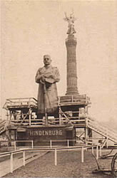 a statue of Hindenburg with the Victory Column in the background